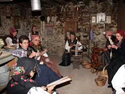 donne nei costumi tradizionali che tessono e filano a Premana Valsassina Lago di Como
